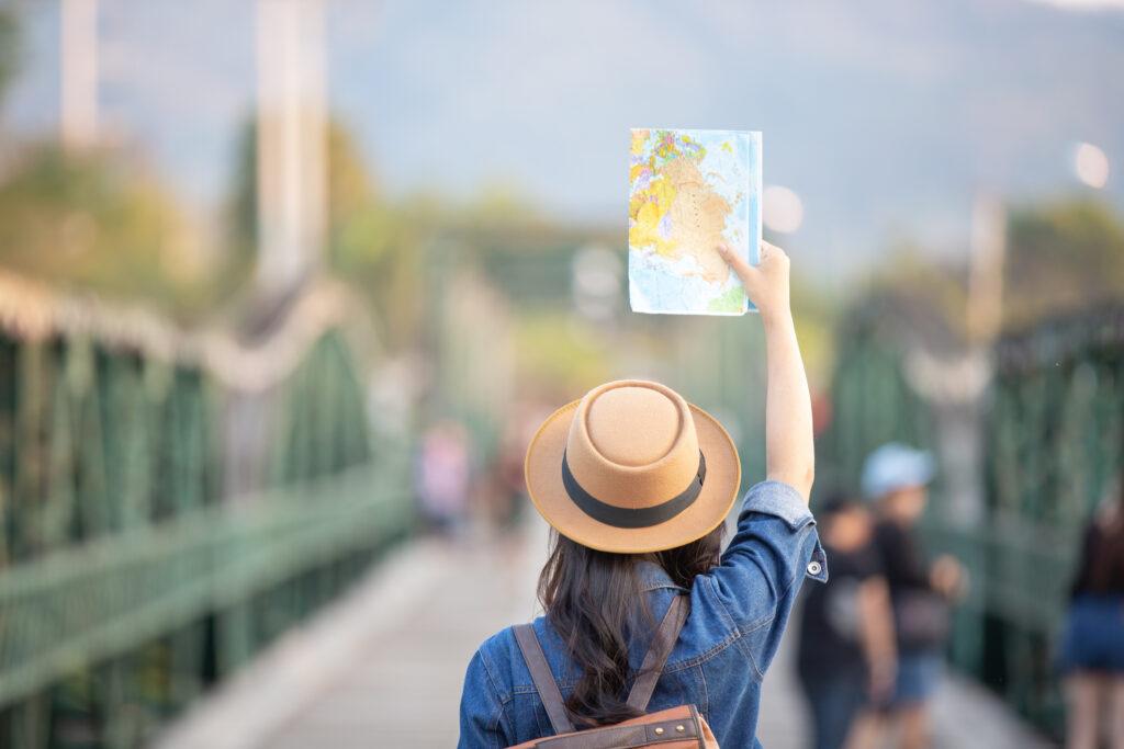 kobieta stojąca tyłem, która trzyma w podniesionej dłoni mapę