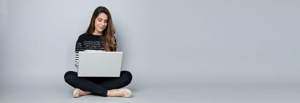 kobieta siedząca na podłodze i trzymająca na kolanach laptop